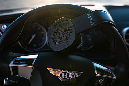 Abyss Diana headphone draped over a steering wheel